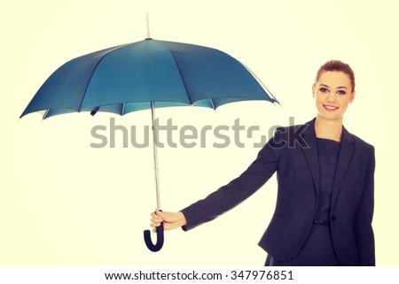 Attractive businesswoman holding an umbrella. - stock photo