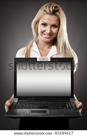 Attractive businesswoman holding laptop with copyspace available on the computer screen - stock photo