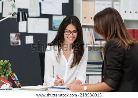 Attractive businesswoman in a meeting in the office with a female colleague smiling as she writes something in a file - stock photo
