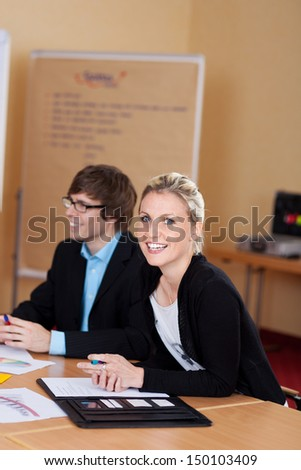 Attractive businesswoman in a meeting sitting at a table with her colleagues turning to smile at the camera - stock photo