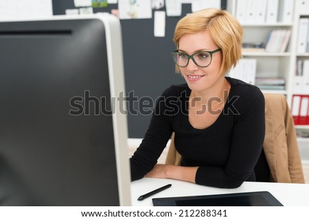 Attractive businesswoman in glasses working in the office sitting at her desk in front of the computer monitor - stock photo