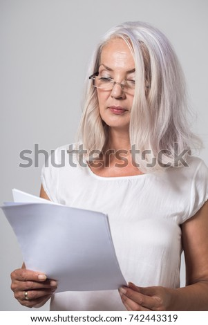 Attractive businesswoman in her fifties wearing spectacles standing reading a handheld document with a serious engrossed expression