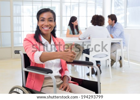Attractive businesswoman in wheelchair gives thumbs up to camera in the office - stock photo
