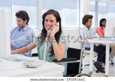 Attractive businesswoman in wheelchair on phone in the office - stock photo