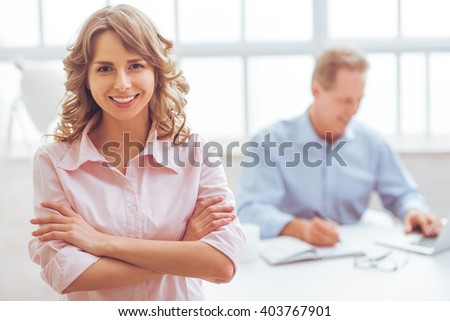 Attractive businesswoman is looking at camera and smiling, on the background businessman working using a laptop - stock photo