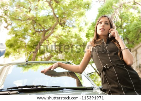 Attractive businesswoman leaning on a car in a tree lined street, having a conversation with her cell phone. - stock photo