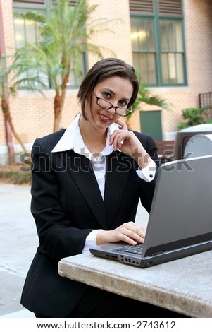 Attractive businesswoman looking at camera using laptop - stock photo