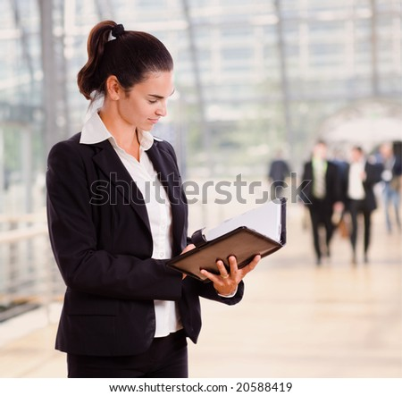 Attractive businesswoman looking at day planner in office lobby. - stock photo