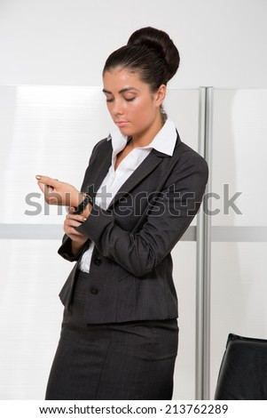 Attractive businesswoman looking at wrist watch, standing in office - stock photo