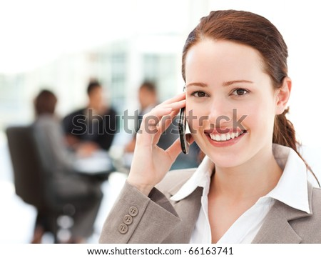 Attractive businesswoman on the phone while her team is working in the background - stock photo