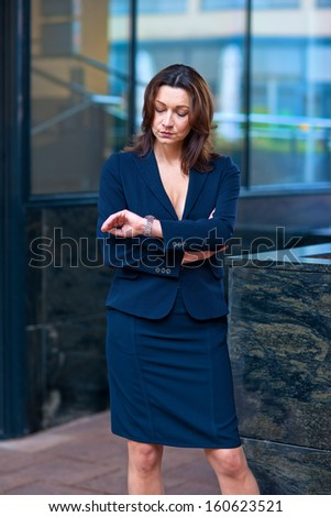 attractive businesswoman outside the office building looking at her wrist watch