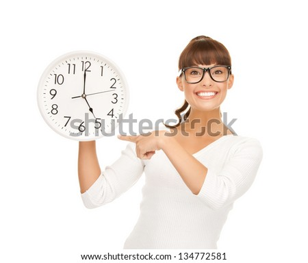 attractive businesswoman pointing her finger at wall clock - stock photo