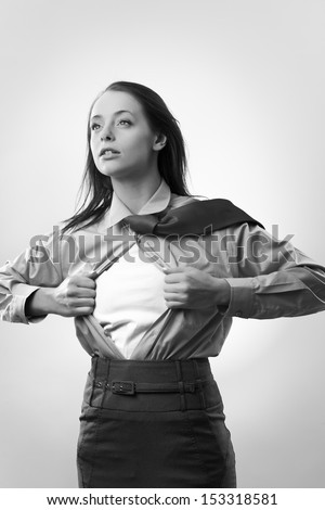 attractive businesswoman pulling her shirt apart doing a superhero businessman poses  - stock photo
