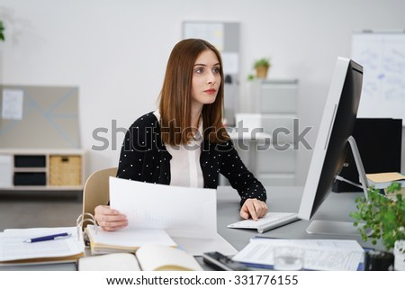 Attractive businesswoman reading information on a desktop monitor with a serious absorbed expression as she holds a paper document in her hand - stock photo