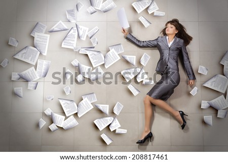 Attractive businesswoman running with papers in hand - stock photo
