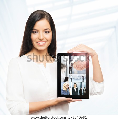 Attractive businesswoman showing the tablet pc with many different business pictures