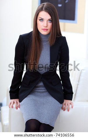 Attractive businesswoman siting on the chair in office - stock photo