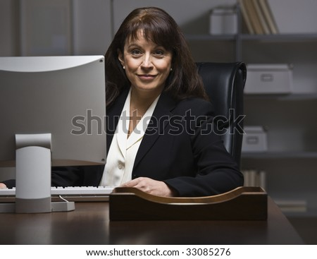 Attractive businesswoman sitting at desk in suit, behind monitor. Looking at camera. Horizontal - stock photo