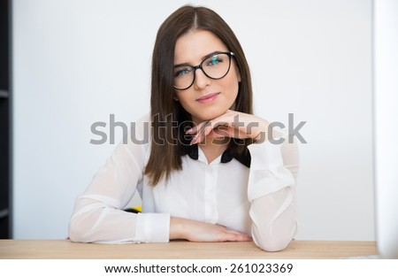 Attractive businesswoman sitting at the table in office - stock photo