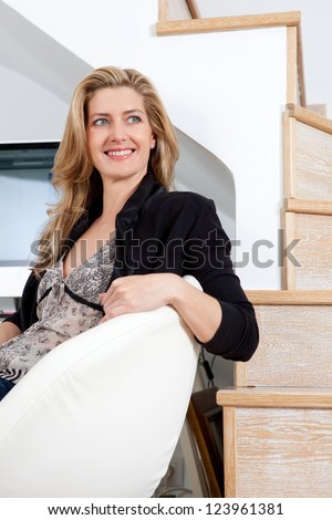 Attractive businesswoman sitting down on her home office chair, next to a wood floor stairwell, smiling.