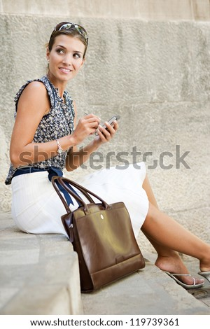 Attractive businesswoman sitting down on stone steps in the city, using a smart phone and smiling.