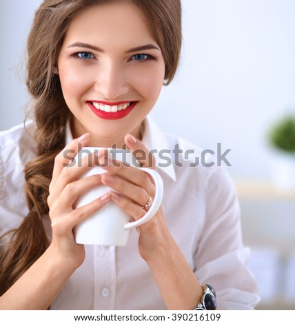 Attractive businesswoman sitting  on desk in the office