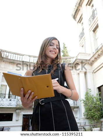 Attractive businesswoman standing in a luxury classic architecture coffee shop terrace, taking notes in her agenda smiling. - stock photo