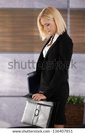 Attractive businesswoman standing in office, holding laptop computer and closing business briefcase. - stock photo