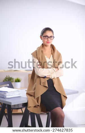 Attractive businesswoman standing near desk in the office. - stock photo