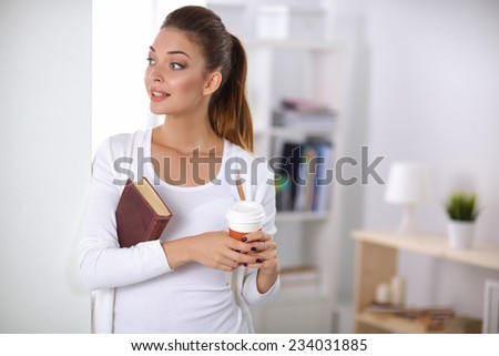 Attractive businesswoman standing  near wall in office - stock photo
