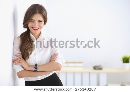Attractive businesswoman standing near wall in office. - stock photo