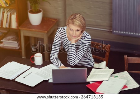 Attractive businesswoman surrounded by paperwork as she sits at her desk working on a laptop computer, high angle view - stock photo