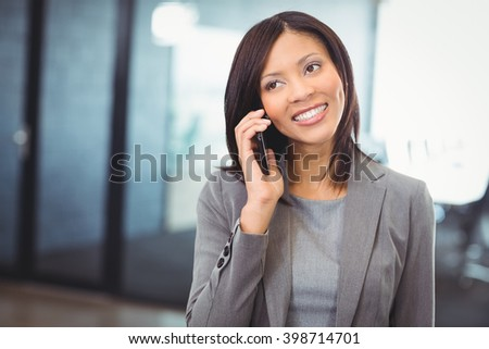 Attractive businesswoman talking on mobile phone - stock photo
