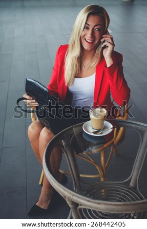 Attractive businesswoman talking on mobile phone during her lunch break in a coffee shop, young woman speaking on a cellphone at a cafe, smiling woman having cell conversation, filtered image - stock photo