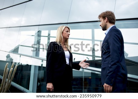 Attractive businesswoman talking with her business partner standing near skyscraper office, confident businesspeople having serious conversation about the work, angry boss discussing with employee - stock photo