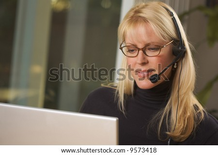 Attractive businesswoman talks on her phone headset. - stock photo