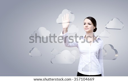 Attractive businesswoman touching cloud icon on screen - stock photo