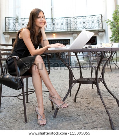 Attractive businesswoman using a laptop computer while having breakfast in a luxurious coffee shop, outdoors.
