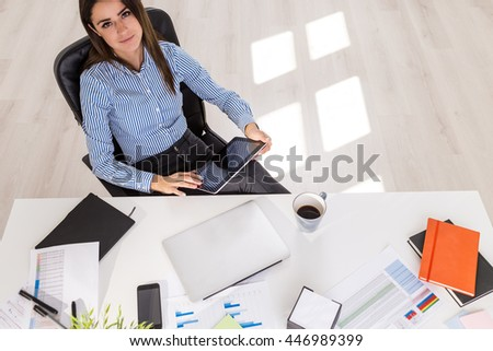 Attractive businesswoman using tablet at office desk with coffee cup, closed laptop, notepads and other items. View from above - stock photo