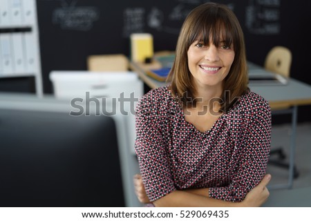 Attractive businesswoman with a friendly welcoming smile leaning forwards on her desk looking directly at the lens