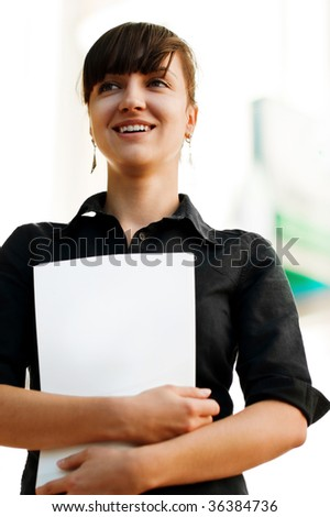 Attractive businesswoman with her arms crossed on a folder - stock photo