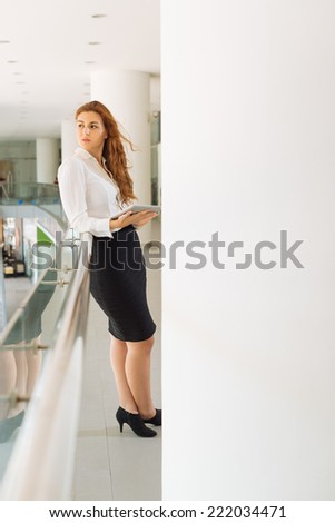 Attractive businesswoman with tablet computer leaning  on railing in office building and looking away  - stock photo