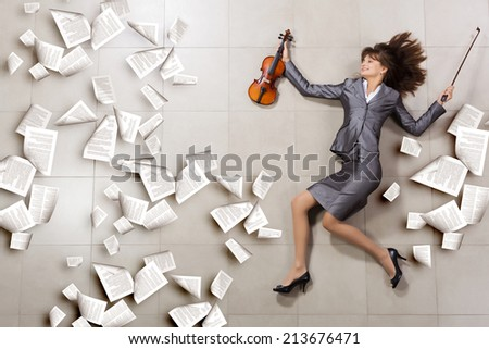 Attractive businesswoman with violin in hands and papers flying in air - stock photo