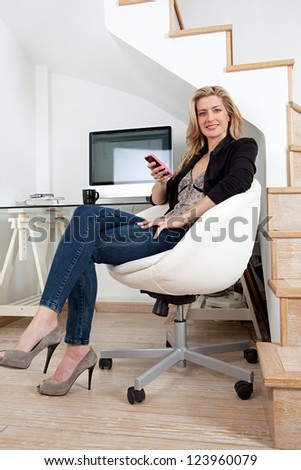 Attractive businesswoman working from home office and using a smart phone while sitting on a modern chair and working at her desk.