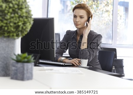 Attractive businesswoman working in green office, talking on mobilephone, using computer. - stock photo