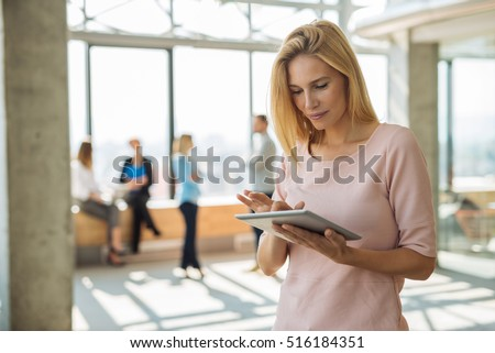 Attractive businesswoman working on a tablet in the office.