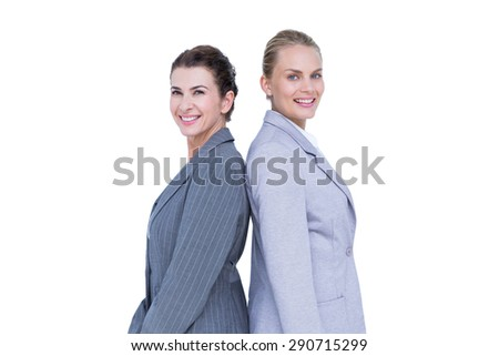 Attractive businesswomen standing back-to-back against white wall - stock photo