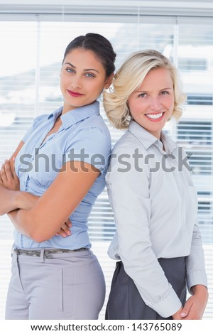 Attractive businesswomen with arms crossed standing back to back in a bright office - stock photo