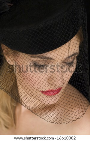 Attractive cabaret girl looking down with a hat and net over her face - stock photo