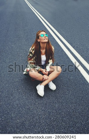 Attractive Californian hipster girl sitting on her cruiser long-board in the middle of asphalt road, fashion model posing with skate board wearing colorful sunglasses,copy space area for content - stock photo